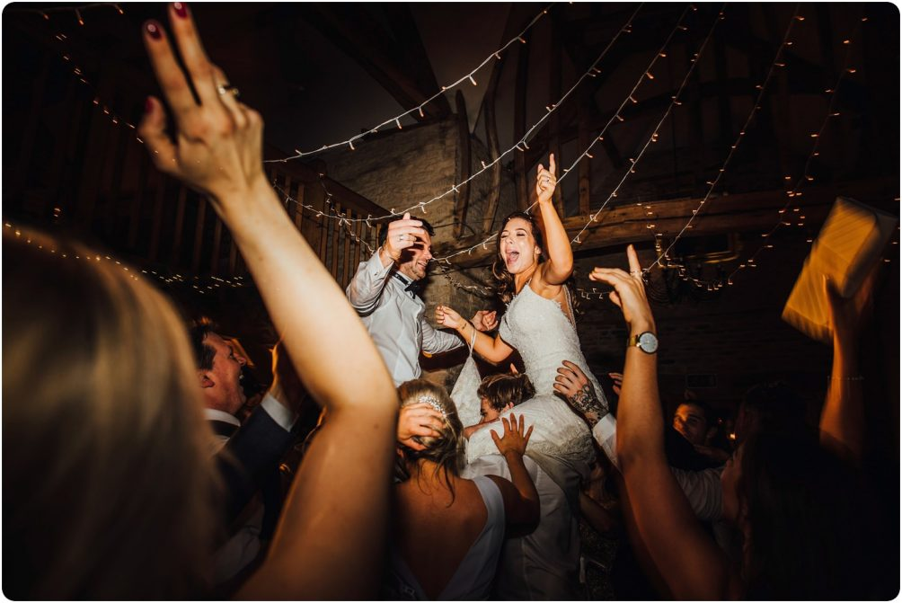 bride and groom on guests shoulders at a kingscote barn wedding