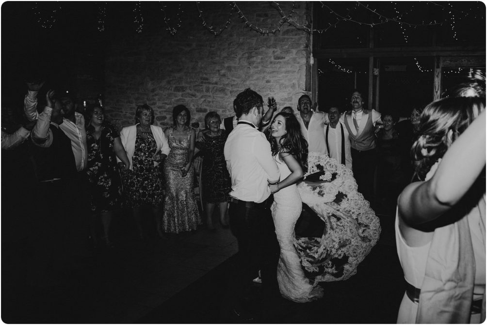bride in enzoani dress dancing in black and white at a kingscote barn wedding