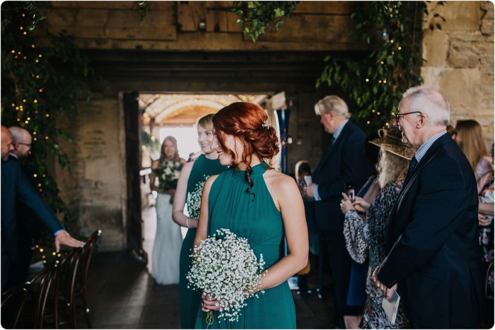 bridesmaid wearing dark green at a stone barn wedding