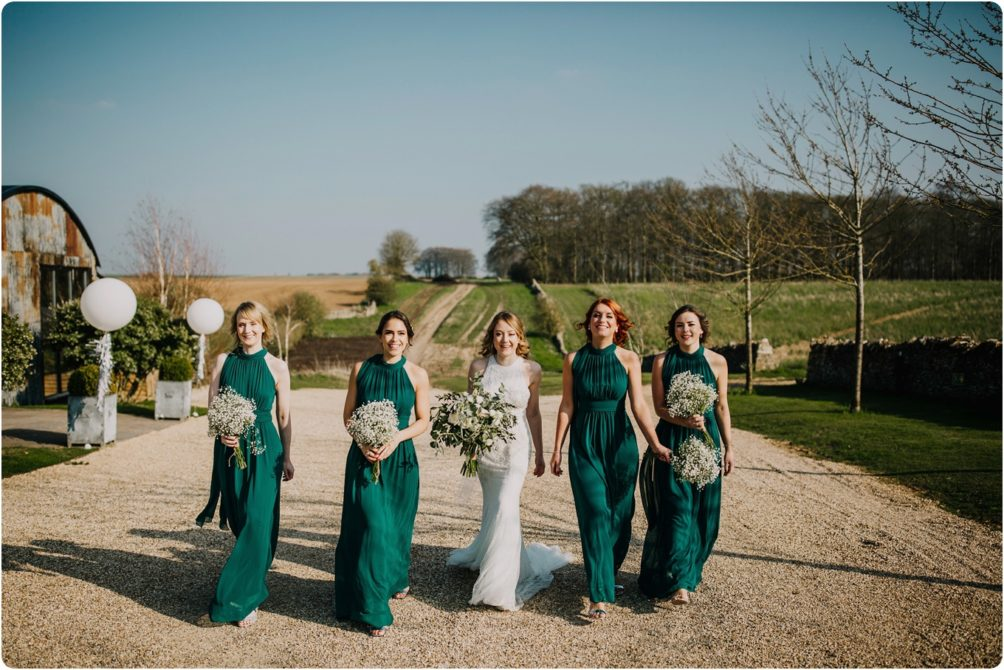 bridesmaids walking together at a stone barn wedding